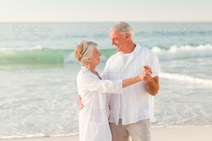 Elderly couple dancing on the beach