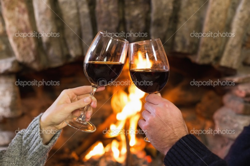 Close-up of hands toasting wineglasses in front of lit fireplace